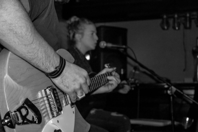 Guitar in foreground and singer in background, small band performing in a pub venue
