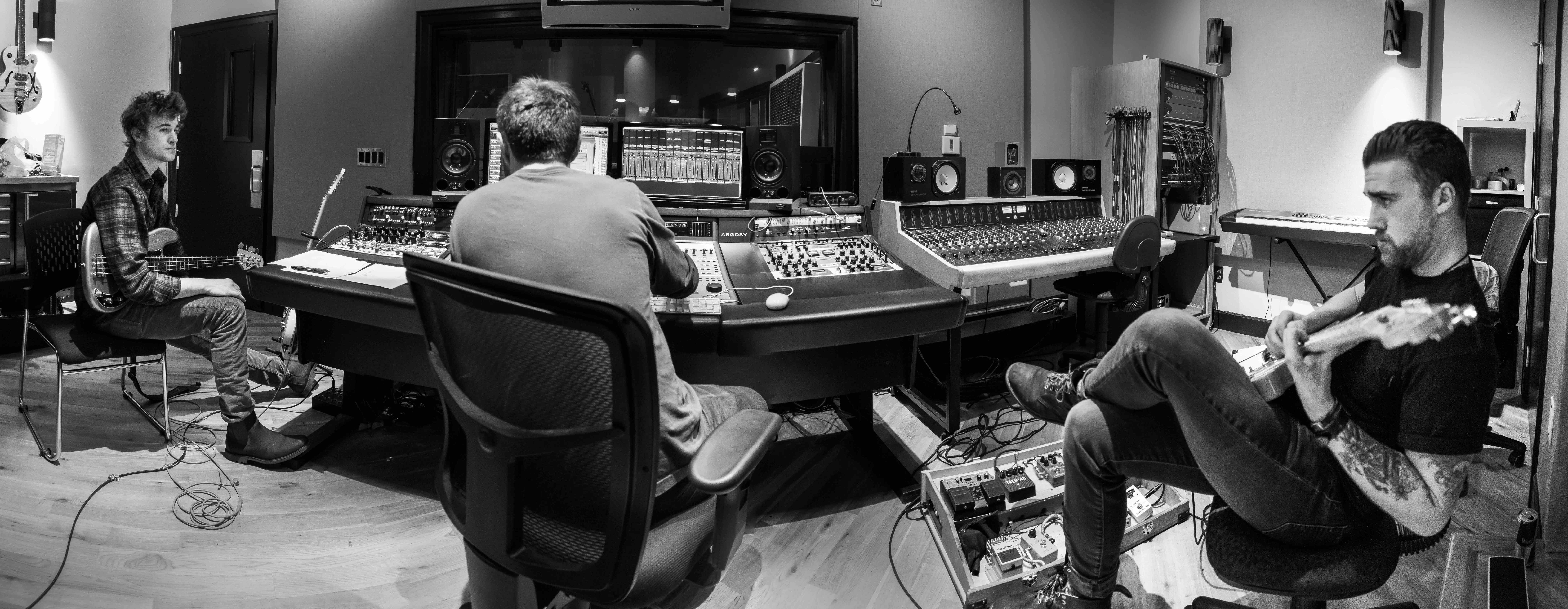 panoramic view of recording studio, guitar, guitarist, bass guitar, bassist, mixer, producer all in the shot as well as the sound board