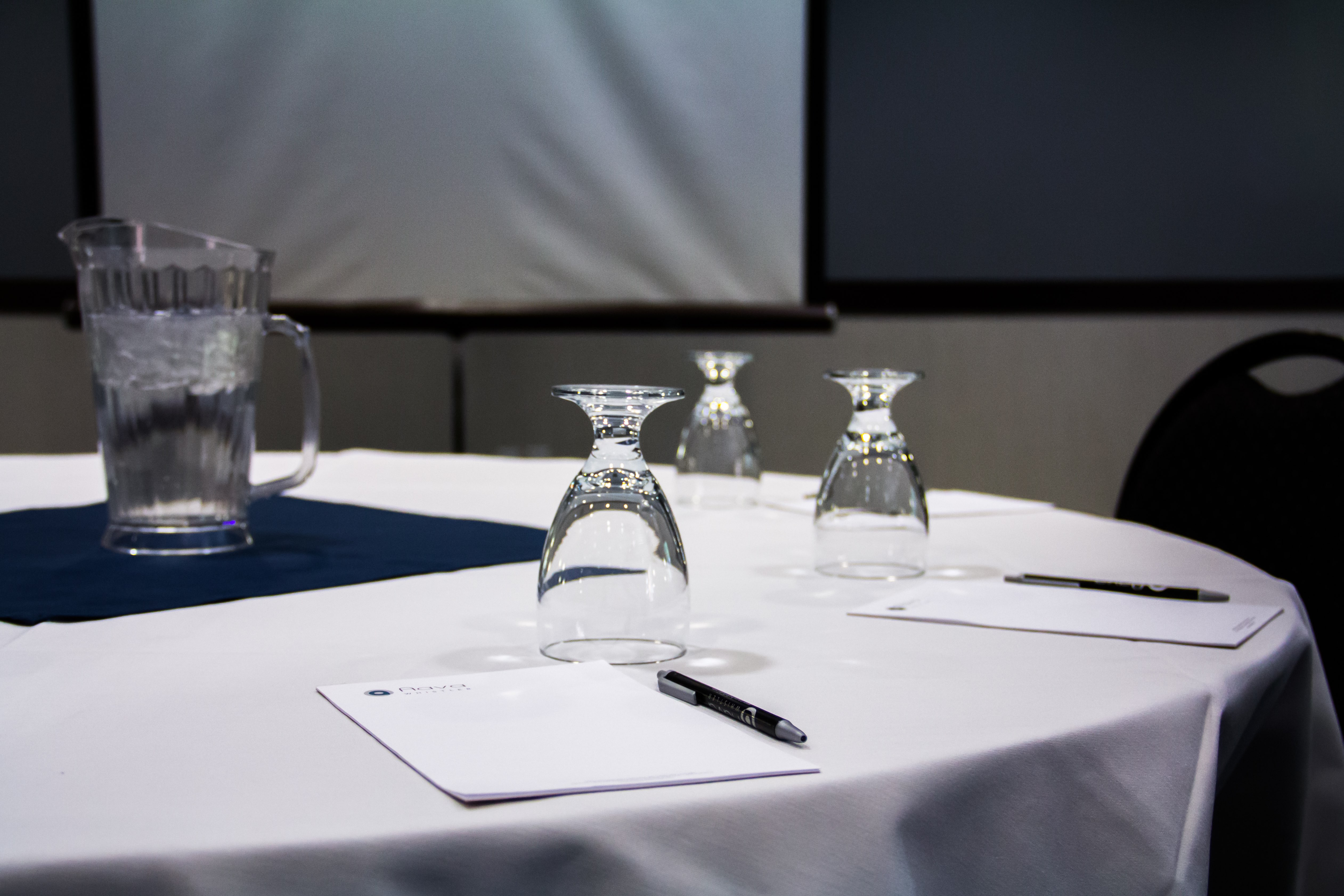 interior photo conference room pen and paper pad on the table jug of water glass decorated landscape