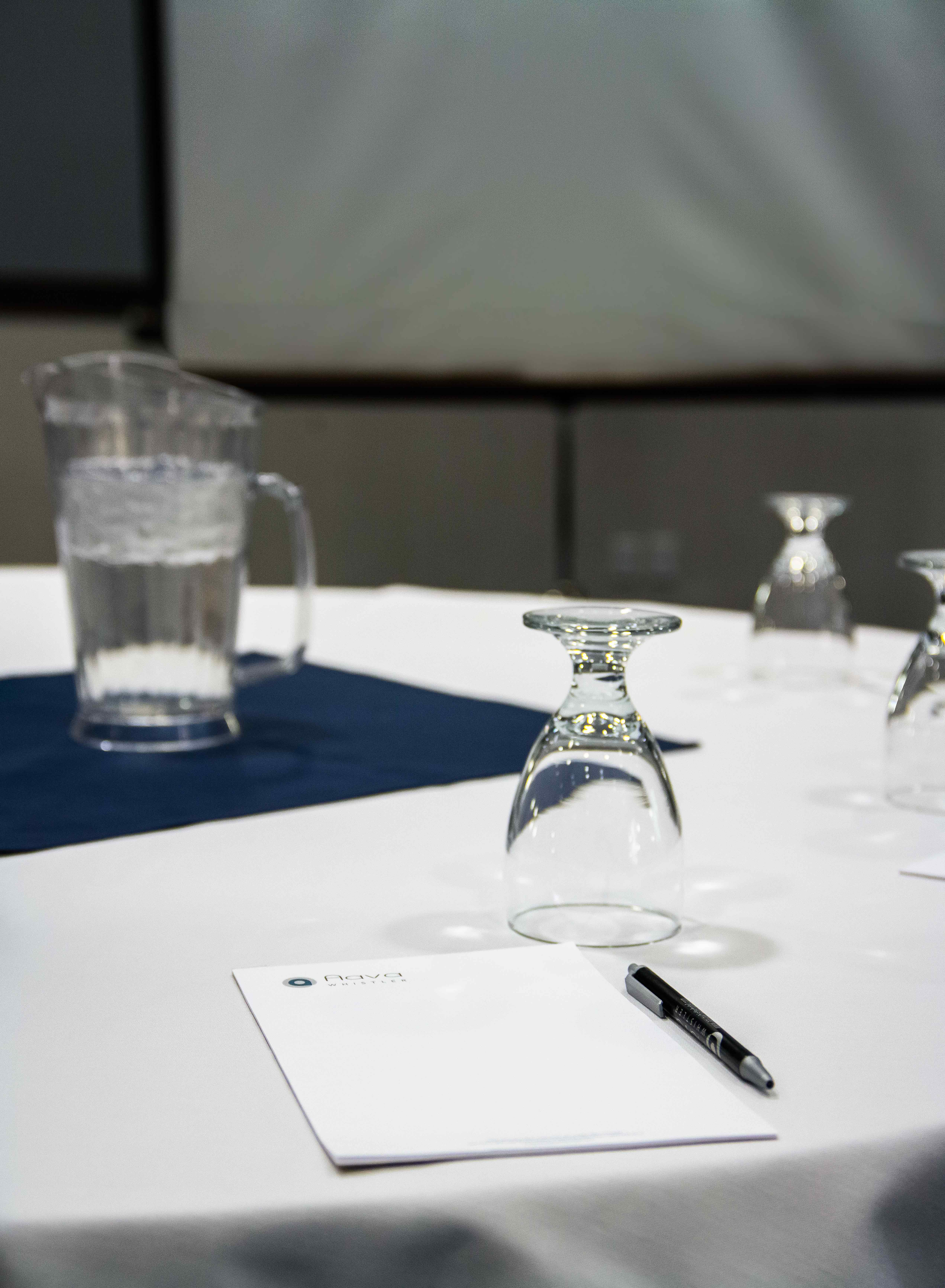 interior photo conference room pen and paper pad on the table jug of water glass decorated portrait