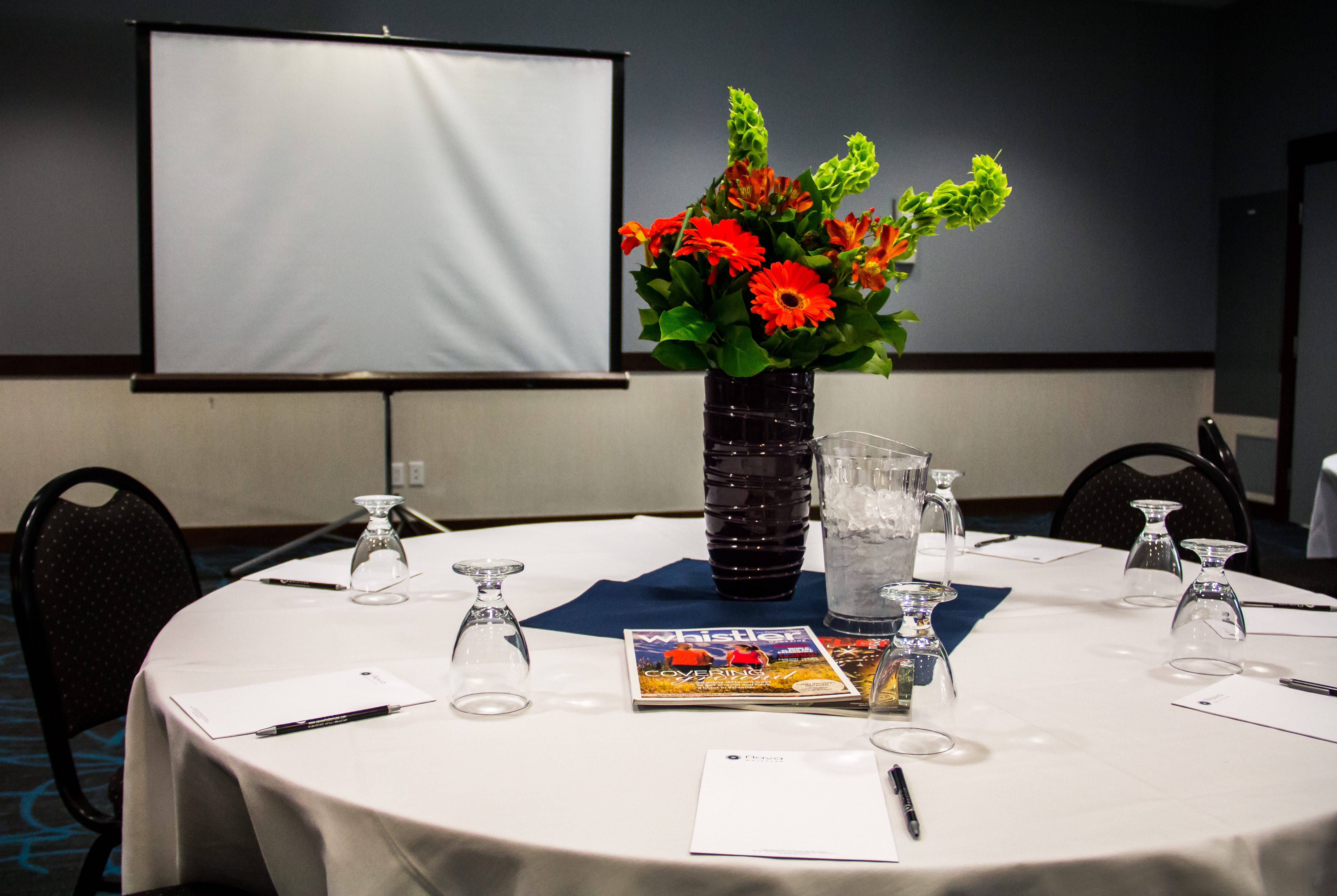 interior photo conference room pen and paper pad on the table jug of water glass decorated landscape floral decoration flowers centrepiece magazines projector screen in background